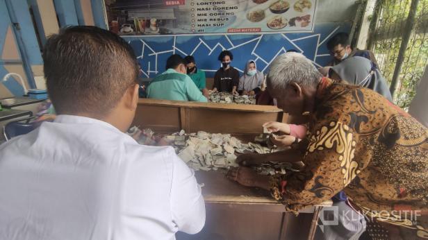 Biyok (pakai baju batik) saat mengeluarkan uangnya dari karung