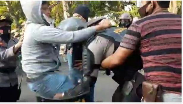 Polisi berseragam lengkap yang tengah mengamankan aksi tolak UU Cipta Kerja dihajar di bagian perutnya dengan menggunakan dengkul oleh orang berpakain bebas hingga terjatuh.