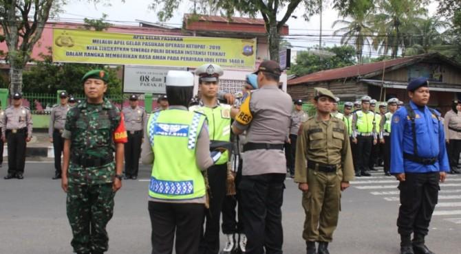 Kapolres Bayuaji memasang tanda personil pengamanan Lebaran 2019 saat apel pasukan di Lapangan Cinduamato Batusangkar.