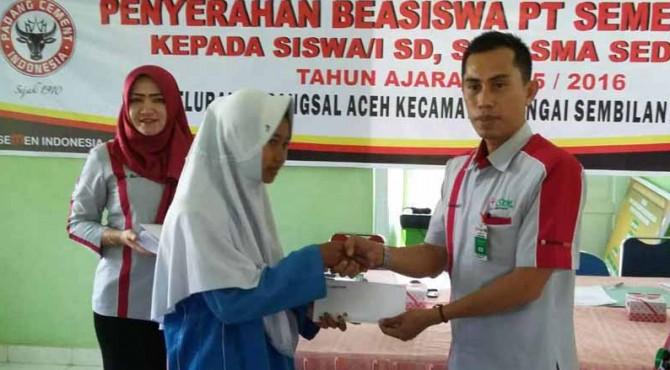 Staf Bidang DikesosLH Biro CSR PT Semen Padang, Yumendri menyerahkan beasiswa kepada salah seorang pelajar di Dumai secara simbolis.