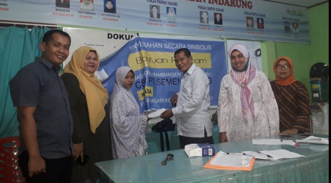 Ketua Forum Nagari Indarung, Darmansyah Siroen (kanan) didampingi sejumlah pengurus Forum Nagari menyerahkan bantuan lebaran kepada salah seorang warga di Kantor Forum Nagari Indarung, Selasa, 28 Mei 2019.