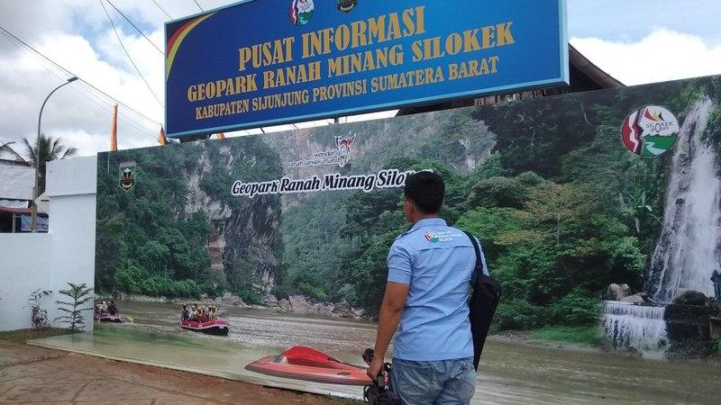 Seorang Warga Melihat Baliho Pusat Informasi Geopark Ranah Minang Silokek di Muaro Sijunjung
