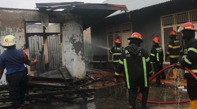 Petugas damkar melakukan proses pendinginan di rumah Pak RT yang terbakar, Senin (11/11/2019)