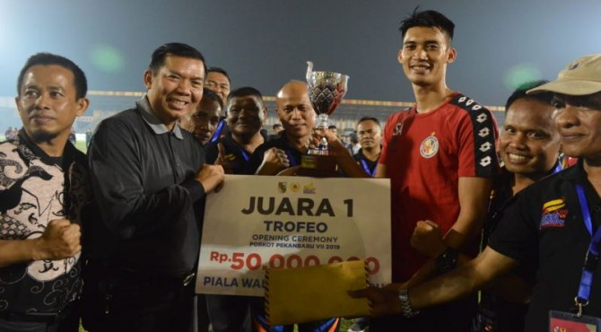 Bek Semen Padang FC, Syaeful Anwar menerima piala setelah menjuarai turnamen trofeo di Pekanbaru.