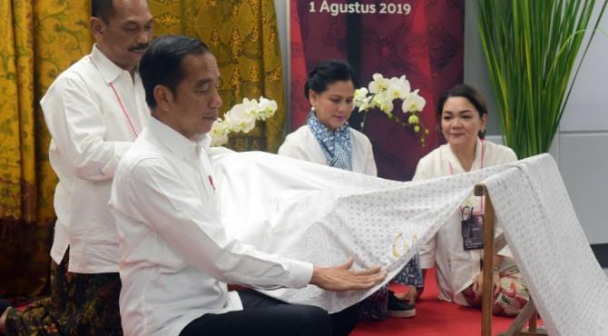 Presiden Jokowi didampingi Ibu Negara Iriana menggores batik menyambut Hari Kemerdekaan RI ke-74, di Stasiun MRT Bundaran Hotel Indonesia, Jakarta, Kamis (1/8)