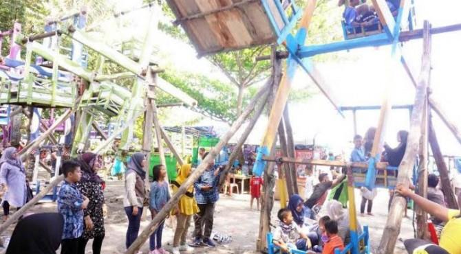 Tampak pengunjung tengah menikmati permainan tradisional Buayan Kaliang di Pantai Gondoriah, Pariaman