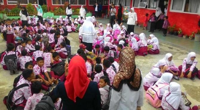 Puluhan murid SD Negeri 07 Indarung, Kota Padang berkumpul di tengah lapangan sekolah saat mengikuti simulasi bencana gempa dan tsunami yang digelar CSR Semen Padang