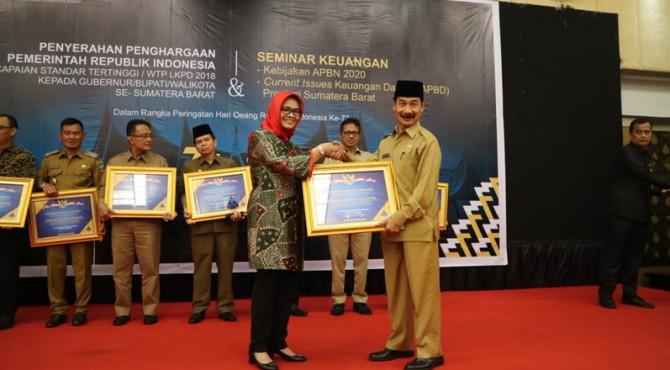 Bupati Solok Selatan Muzni Zakaria menerima Piagam penghargaan CST dari Sekretaris Direktur Jenderal Perbendaharaan Negara, Wiwi Hadayaningsih, di Ballroom Hotel Pangeran Beach, Senin (21/10/2019)