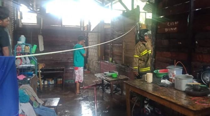 Petugas Damkar Kota Solok bersama warga memadamkan api