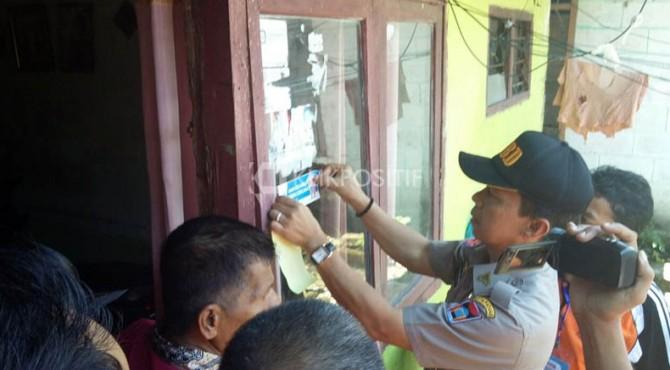 Kepala BPBD Padang Edi Hasymi menempelkan stiker di rumah Keluarga Cerdas Bencana, Senin (13/03/2017)