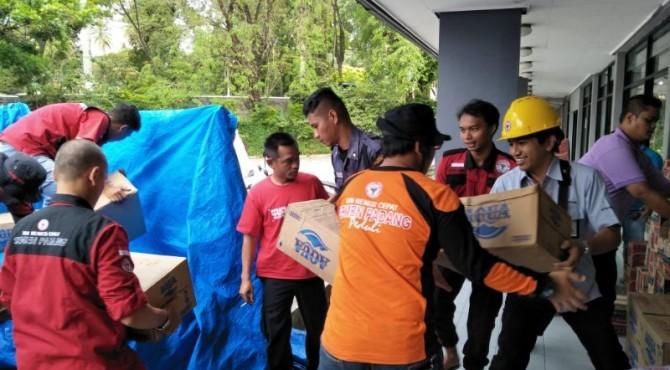 Anggota TRC Semen Padang tengah menaikan bantuan sembako ke atas mobil Pick Up untuk dibawa ke lokasi bencana banjir di Bengkulu