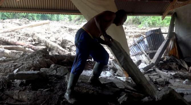 Ultra Caniago (51)  mengangkat puing-puing hasil amukan alam yang memporak porandakan rumahnya