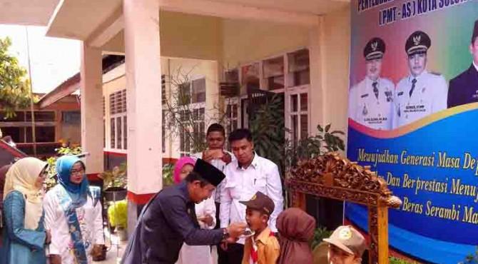 Sekda Kota Solok Rusdianto memberikan kudapan PMT-AS kepada salah seorang murid SD N 14 KTK