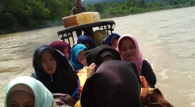 Siswa MAS Merdeka Tampor Paloh melintasi Sungai Tamiang menggunakan perahu kayu, Sabtu (16/02)
