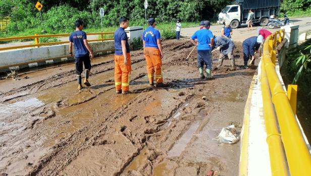 Personil Damkar membersihkan material longsor di badan jalan dan jembatan Nagari Tanjung Alam
