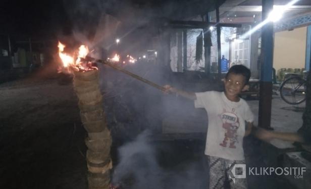 Terlihat seorang anak kecil sedang bersuka cita membakar tempurung yang telah disusun pada sebuah kayu di Kampung Maligi