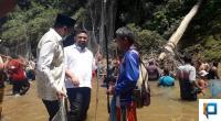 Audy Joinady (berpeci) bersama Erick Hariyona berbaur dengan masyarakat mengambil ikan di Sungai Batang Lapu, Lubuk Godang.