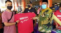 Plt Walikota Padang  Hendri Septa (kanan) menyerahkan kaos bertuliskan Ayo Vaksin! dari Semen Padang kepada pedagang.