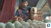 Seorang pedagang memindahkan telur itik yang dijual
