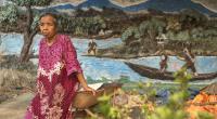 Jahri duduk di halaman rumahnya. Diorama di dinding rumah dibuat pada 1984 menceritakan bagaimana Jahri dan keluarganya hidup dari kekayaan Batang Hari yang melimpah