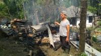 Bambang Sugiatno tengah menyaksikan sisa puing-puing kebakaran kandang kambing miliknya.