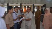 Asisten dua bidang ekonomi pembangunan Solsel Putra Nusa menyerahkan santunan Koperasi DWP kepada Pelajar yatim dan kurang mampu, di Aula Kantor Bupati Solsel, Selasa, 14 Januari 2020