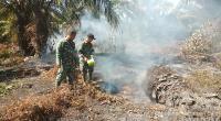 Petugas saat memadamkan api dengan peralatan seadanya