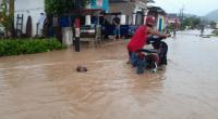 Warga saat berupaya menerobos banjir dengan mendorong kendaraannya