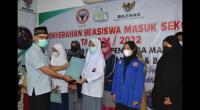Kepala Pelaksana Harian UPZ Baznas Semen padang Muhammad Arif menyerahkan bantuan beasiswa pendidikan kepada perwakilan pelajar.