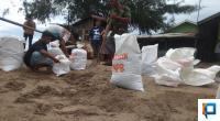 Warga Bergotong Royong Mengisi Karung Dengan Pasir Untuk Mengantisipasi Gelombang Susulan