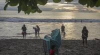 Warga berwisata di kawasan pantai Padang dengan saling menjaga jarak.