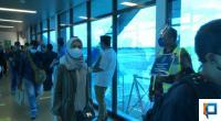 Penumpang Bandara yang Datang Disambut Petugas yang Menyampaikan Pesan 3M + D