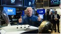 Richard Branson berfoto di depan miniatur pesawat tur antariksa Virgin Galactic pada 28 Oktober 2019.